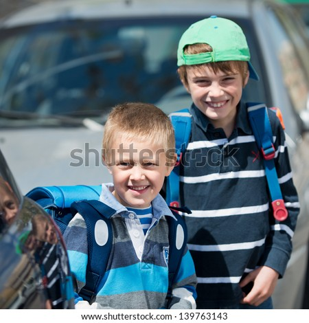 Smiling Schoolchildren waiting for something at the back of parked car - stock photo