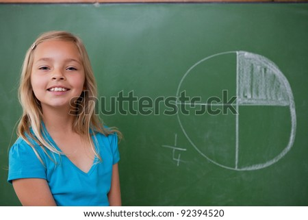 Smiling schoolgirl learning the divisions on a blackground - stock photo
