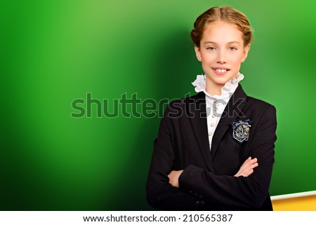 Smiling schoolgirl standing near the blackboard at a classroom. Education. - stock photo