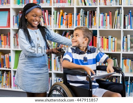 Smiling schoolgirl standing with disabled boy on wheelchair in library - stock photo