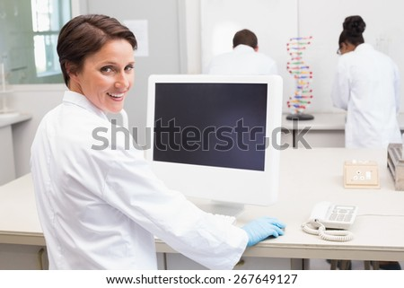 Smiling scientist using computer while colleagues working in the laboratory - stock photo