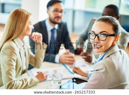 Smiling secretary in eyeglasses looking at camera in working environment - stock photo