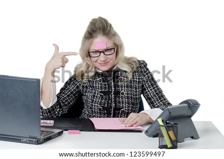 Smiling secretary pointing the pink memo note on her forehead - stock photo