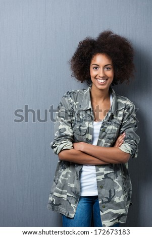 Smiling self-assured young African American woman standing leaning against a grey wall with her arms folded smiling at the camera - stock photo
