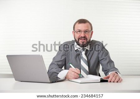 smiling senior businessman with laptop sitting at the desk - stock photo