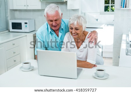 Smiling senior couple looking into laptop in kitchen at home - stock photo