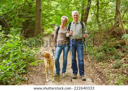Smiling senior couple on a hike walking with a dog in a forest - stock photo