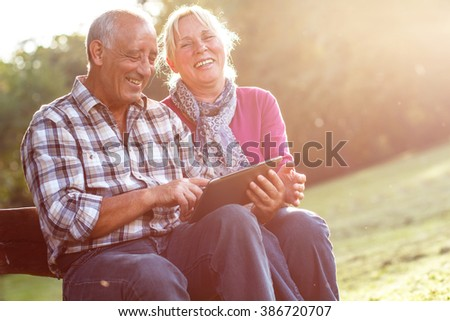 Smiling senior couple sitting on a park bench on sunny autumn day and looking something on a tablet. - stock photo
