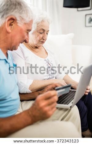Smiling senior couple using laptop at home - stock photo