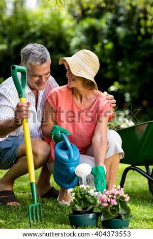 Smiling senior couple with gardening equipment at yard - stock photo