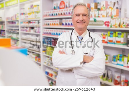 Smiling senior doctor with arms folded in the pharmacy - stock photo