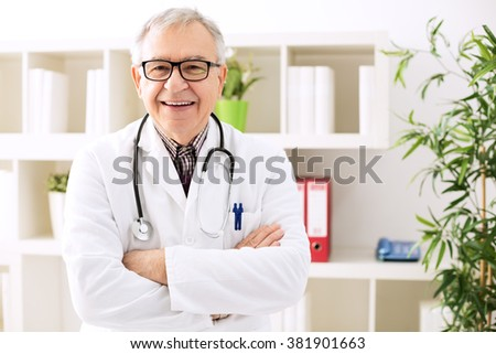 Smiling senior doctor with stethoscope in hospital - stock photo
