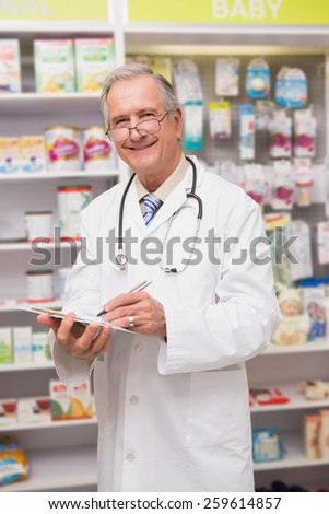 Smiling senior doctor writing on clipboard in the pharmacy - stock photo