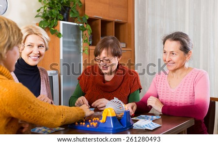 Smiling senior female friends having fun with table game indoor  - stock photo