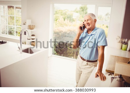 Smiling senior man on a phone call in the kitchen - stock photo
