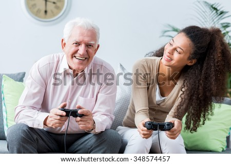 Smiling senior man playing on the console - stock photo