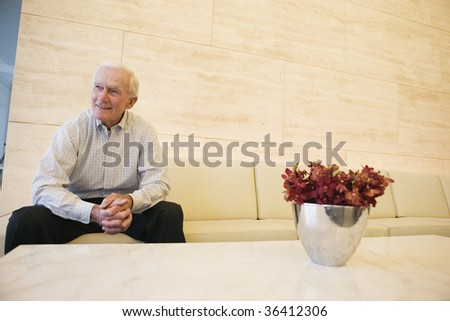 Smiling senior man waiting patiently in an office lobby. - stock photo