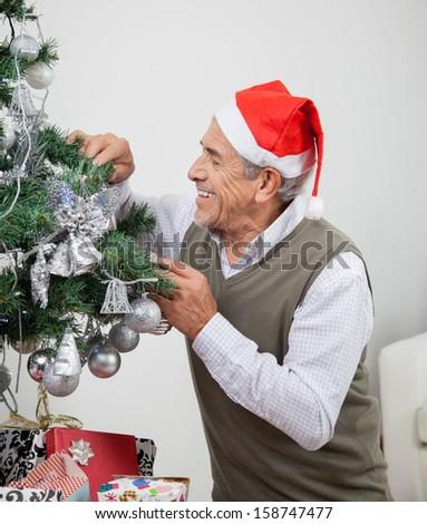 Smiling senior man wearing Santa hat decorating Christmas tree at home - stock photo