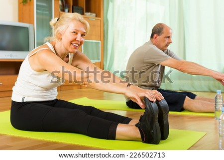Smiling senior mature couple doing morning exercises indoor - stock photo