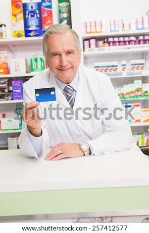 Smiling senior pharmacist holding credit card in the pharmacy - stock photo