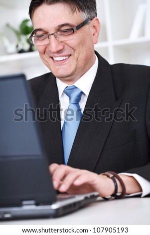 smiling senior successful businessman  working on laptop in office - stock photo