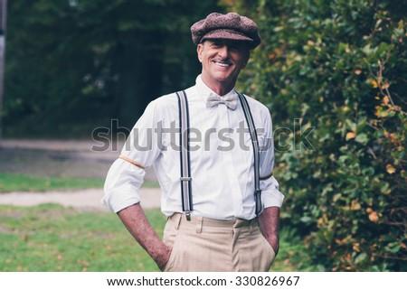 Smiling senior vintage fashion man enjoying his garden. - stock photo