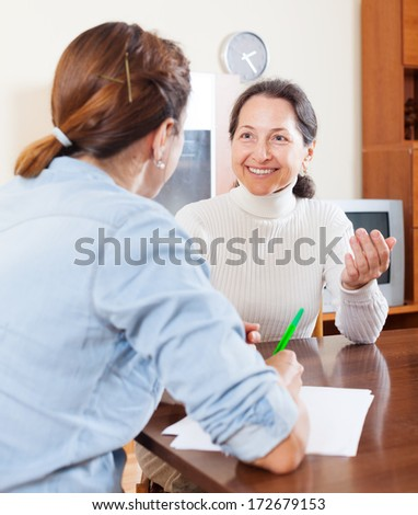 Smiling senior woman answer questions of social worker in home - stock photo