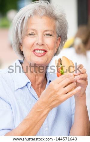 Smiling senior woman eating some fish - stock photo