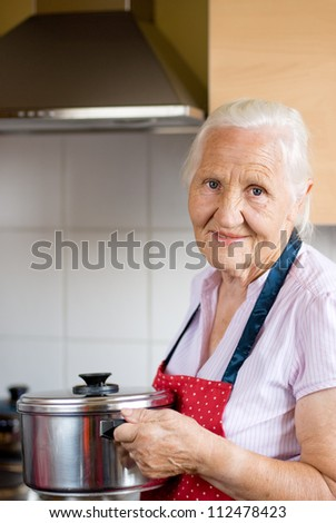 Smiling senior woman in a kitchen is holding a casserole - stock photo