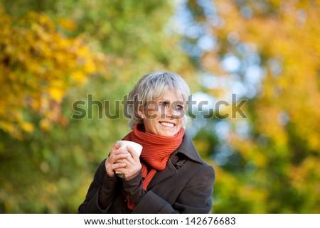Smiling senior woman in jacket enjoying coffee in park - stock photo