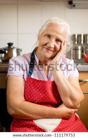 Smiling senior woman in the kitchen - stock photo