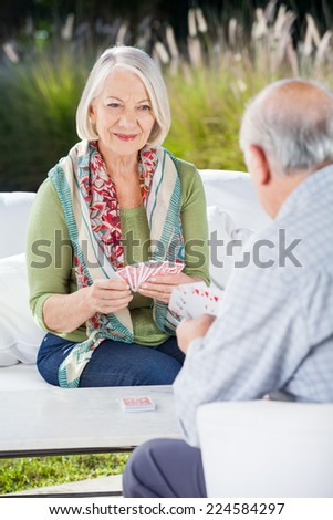 Smiling senior woman playing cards with man at nursing home - stock photo