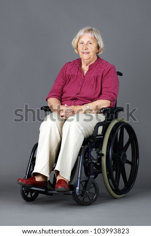 Smiling senior woman seated in a wheelchair, either handicapped or disabled, looking at camera over neutral grey background. - stock photo