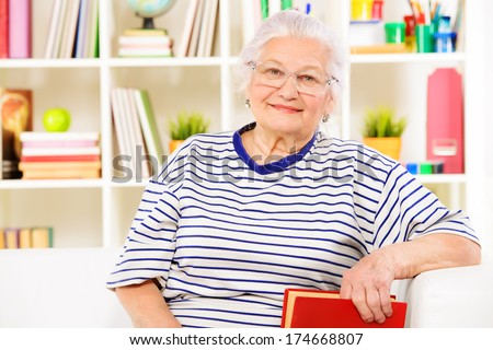 Smiling senior woman sitting at home on a sofa and reading a book. - stock photo