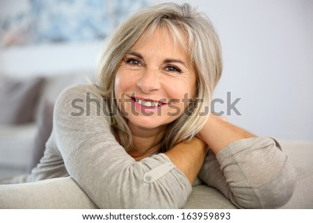 Smiling senior woman sitting in couch at home - stock photo