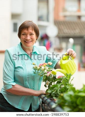 Smiling senior woman watering decorative flowers on balcony - stock photo