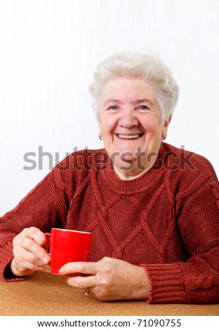 Smiling senior  woman with a cup of coffee in hands - stock photo