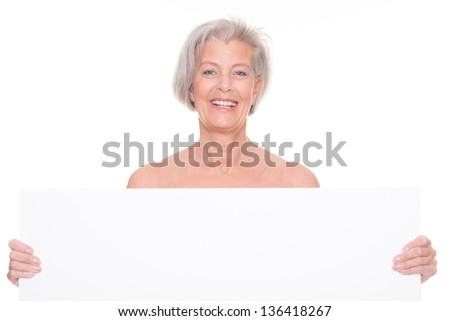 Smiling senior woman with blank sign in front of white background - stock photo