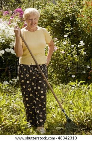 Smiling senior woman with rake in the garden - stock photo