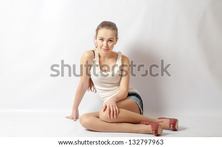 Smiling sexy blond woman in white shirt and jeans shorts sitting on a floor on white - stock photo