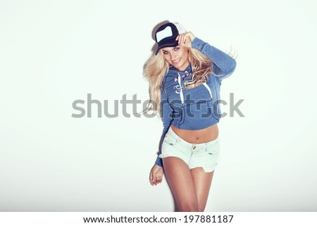 Smiling sexy blonde beautiful woman posing in studio wearing fashionable clothes. - stock photo
