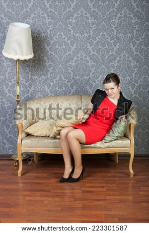 smiling sexy lass sits on a sofa - stock photo
