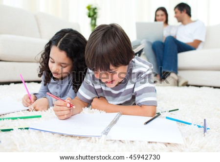 Smiling siblings drawing lying on the floor - stock photo