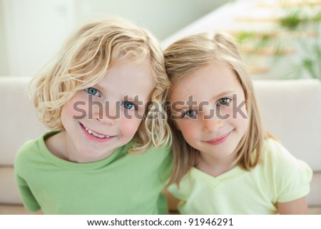 Smiling siblings together on the sofa - stock photo