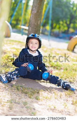 Smiling skater boy in helmet sitting near the tree - stock photo