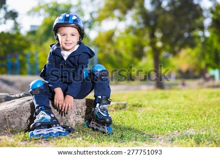 Smiling skater boy sitting on the stone in the park - stock photo