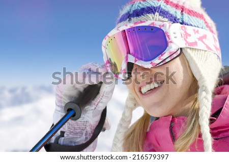 Smiling skier adjusting goggles - stock photo