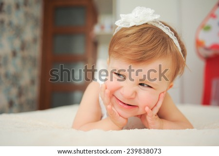 smiling sly girl lying in bed  - stock photo