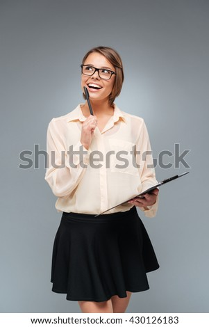 Smiling smart beautiful woman thinking about something and holding folder over gray background - stock photo