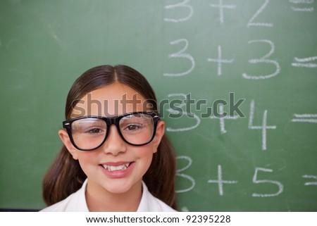 Smiling smart schoolgirl posing in front of a blackboard - stock photo